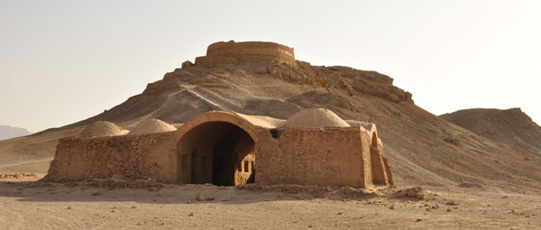 A Zorastrian fire temple, used for ancient sky burial rituals, looks out over an abandoned Zorastrian mud building in the desert around Yazd.