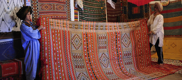 Some Saharan nomadic carpet salesmen, earnestly showcasing their wares in a desert Kasbah near the Atlas mountains.