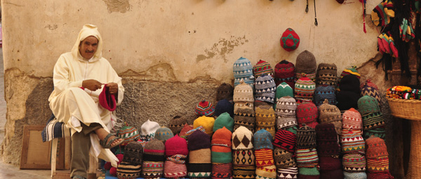 Juraba clad local selling hats  in the back alleys of the beautiful seaside fort of Essaouira. Famous retreat of Jimi Hendrix and numerous other artisans.